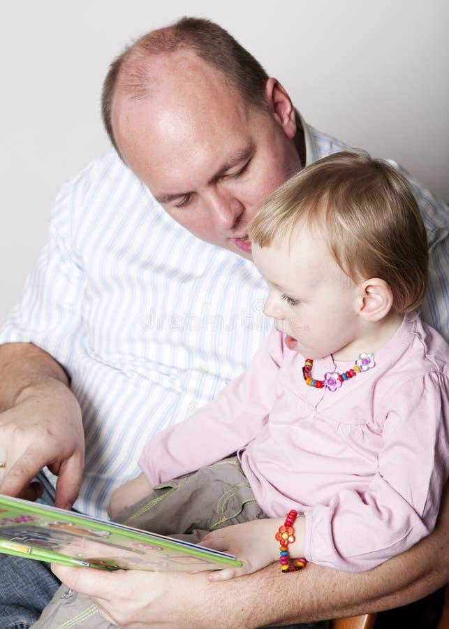 behandla som ett barn dotterfaderavläsning royaltyfri fotografi