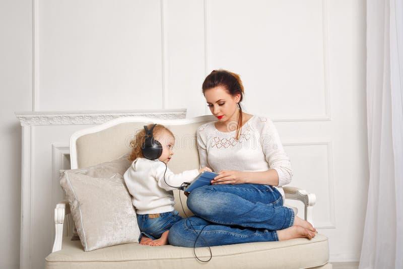 behandla som ett barn dottermodern lyssnar musik till arkivfoton