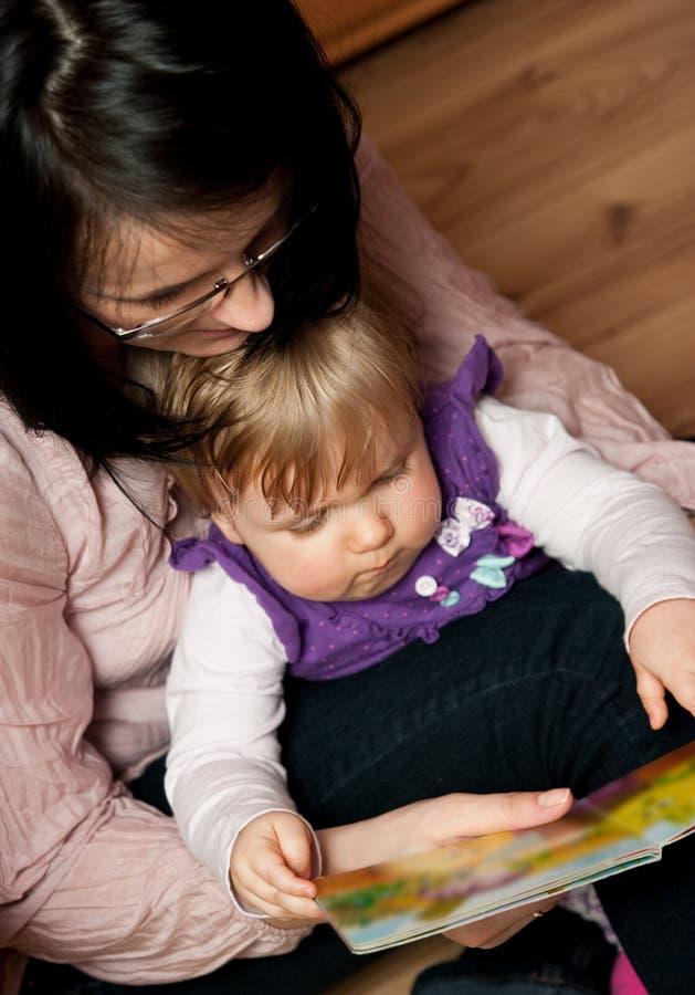 behandla som ett barn dottern som modern läser till royaltyfri foto