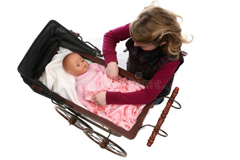 behandla som ett barn - för dockan som flickan ner ser ung royaltyfria foton