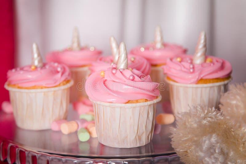 Behandla som ett barn först begreppet för flickafödelsedagpartiet Godisstång med söta enhörningkakor och dekorobjekt i ljusa rosa arkivfoton