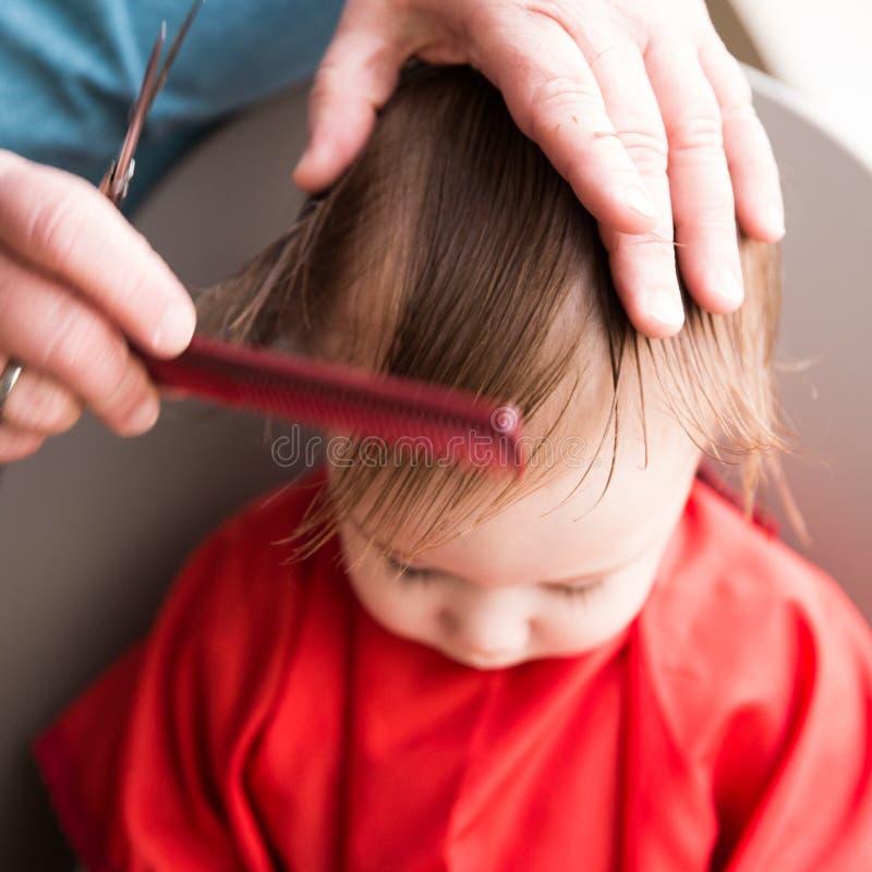 Behandla som ett barn första frisyr för pojkar arkivfoto