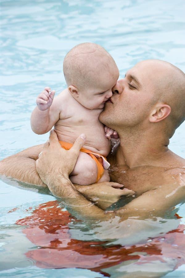 behandla som ett barn fadern som ger kysspölsimning royaltyfria foton