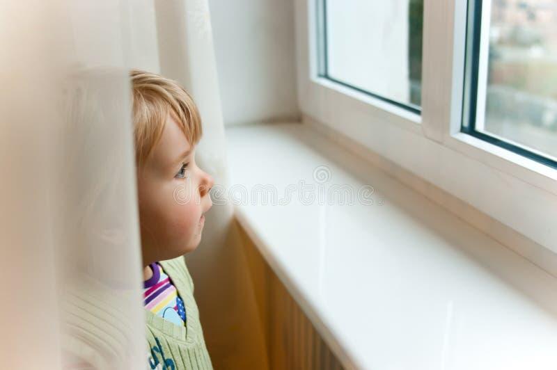 behandla som ett barn flickafönstret arkivbilder