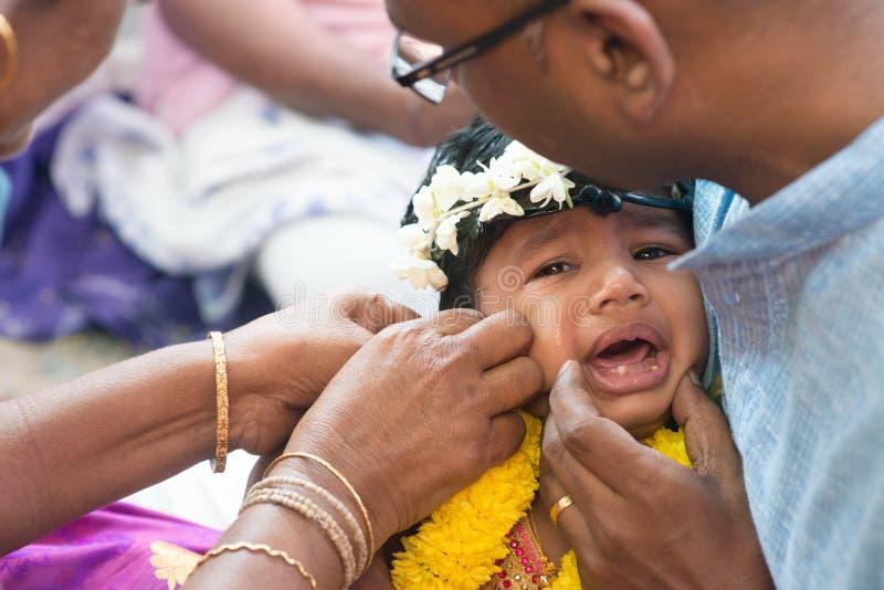 Behandla som ett barn flickagråt i genomträngande ceremoni för det Hindus örat royaltyfria bilder