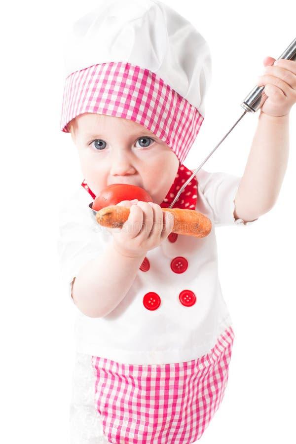 Behandla som ett barn flickakocken som bär en kockhatt med grönsaker och pannan som isoleras på vit bakgrund. royaltyfria bilder