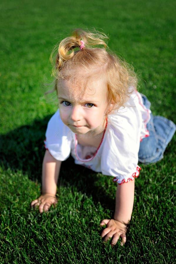 Behandla som ett barn flickakrypningen på det gröna gräset i parkera royaltyfri fotografi