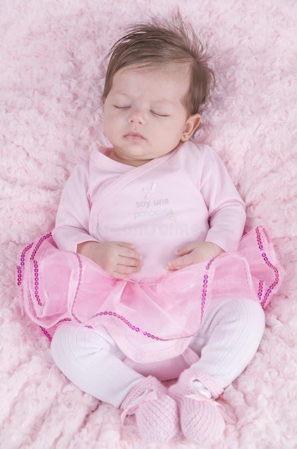 Behandla som ett barn flickan som är sovande på rosa säng Nyfött Rosa kläder royaltyfria foton