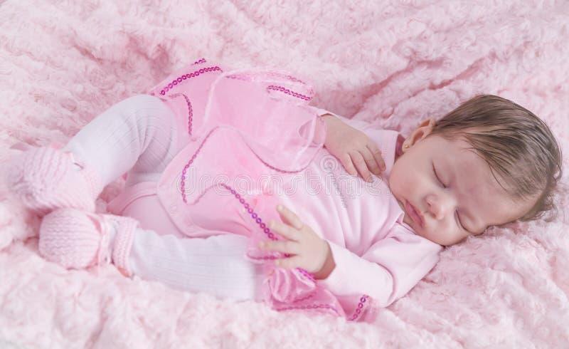 Behandla som ett barn flickan som är sovande på rosa säng Nyfött Rosa kläder arkivfoto