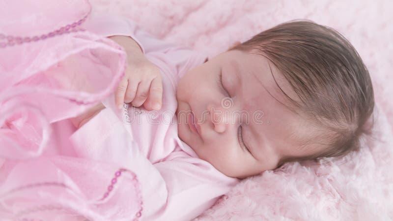 Behandla som ett barn flickan som är sovande på rosa säng Nyfött Rosa kläder arkivbild