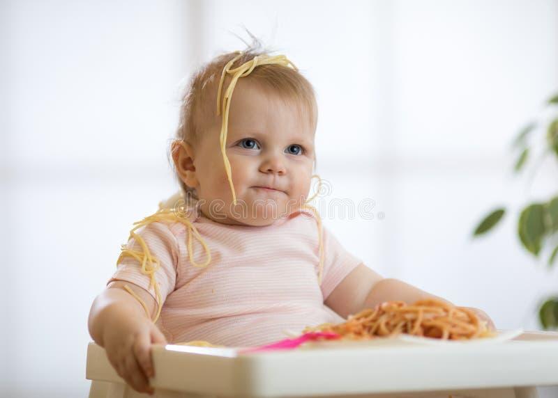 Behandla som ett barn flickan som äter smutsig spagetti arkivfoton