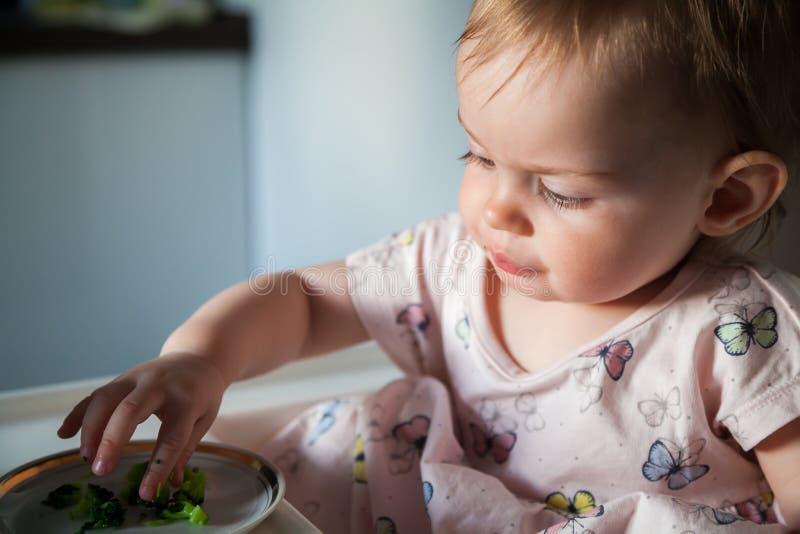 Behandla som ett barn flickan som äter stycken av broccoli royaltyfria foton