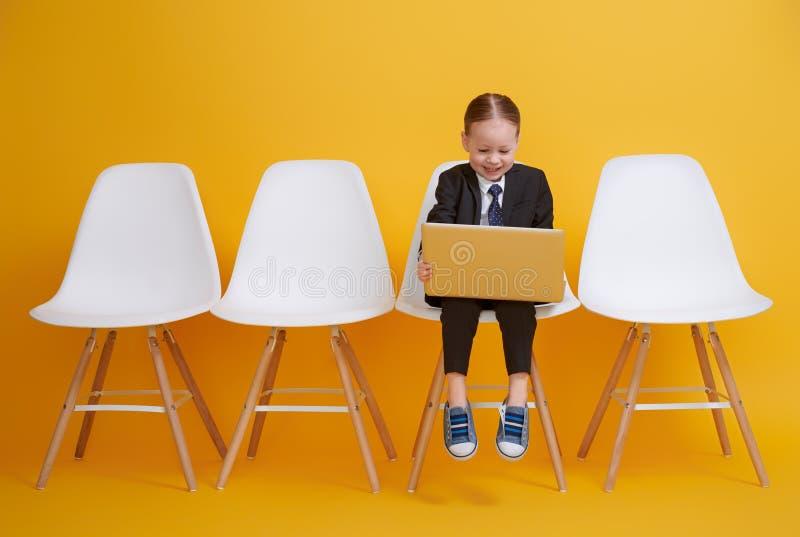 Behandla som ett barn flickan som arbetar p? en dator arkivfoto