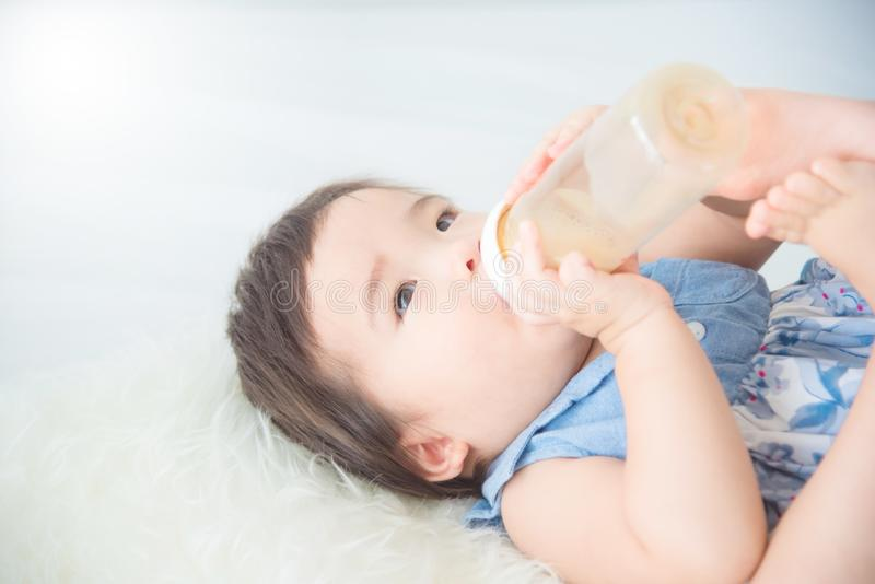 Behandla som ett barn flickan som att rymma mjölkar flaskan och att dricka av henne arkivbilder