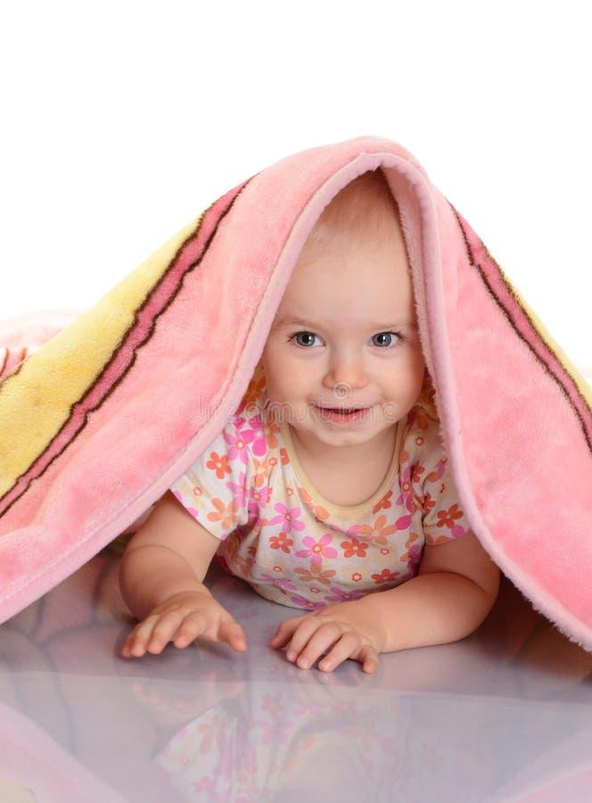 Behandla som ett barn flickan döljer under filten över vitbakgrund fotografering för bildbyråer