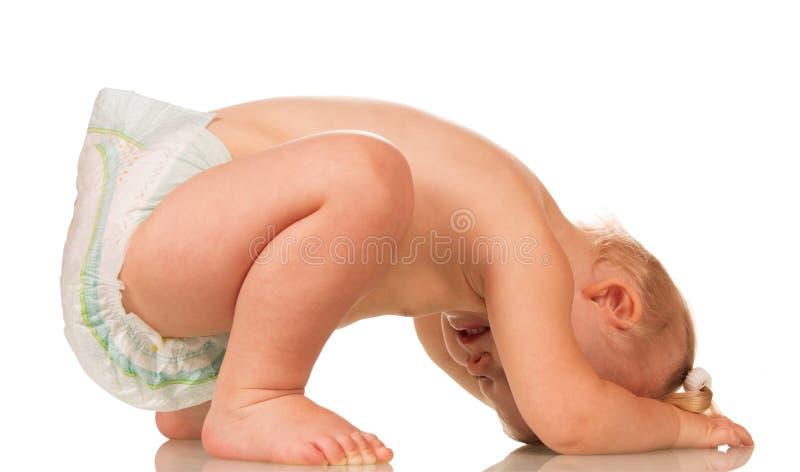 Behandla som ett barn flickan som den isolerade begynnande disponibla blöjan är uppochnervänt royaltyfri foto