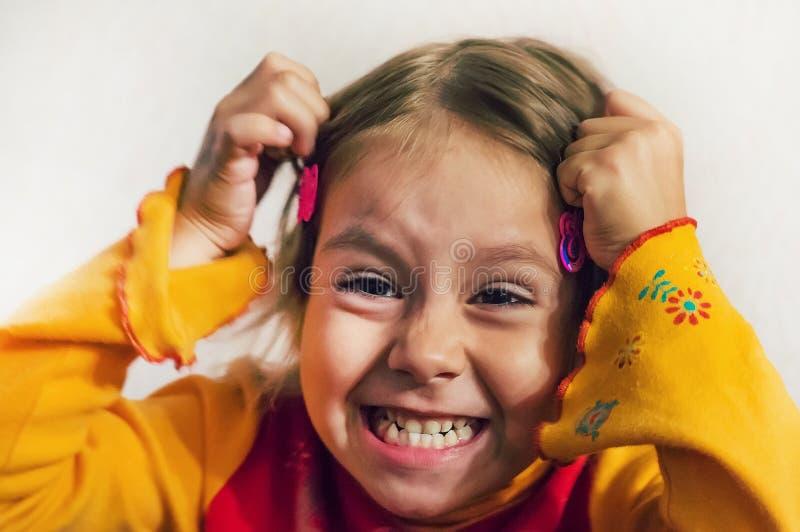Behandla som ett barn flickan gör en grimas på hennes framsida royaltyfria bilder