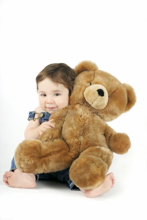 behandla som ett barn flickan henne som kramar nalle arkivfoto