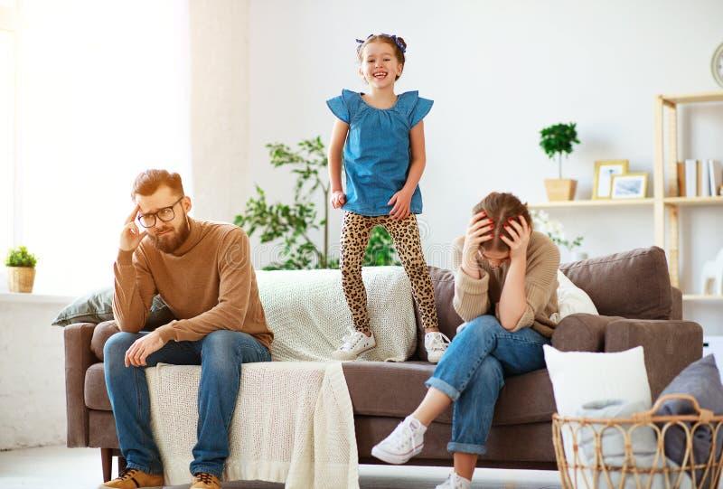 Behandla som ett barn flickan som hoppar och att skratta, och att ha gyckel, föräldrar belastade med huvudvärk, styggt busigt fotografering för bildbyråer