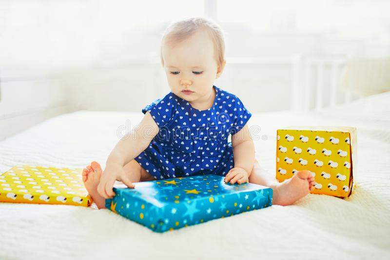 Behandla som ett barn flickan i blå klänning som firar hennes första födelsedag och packar upp hennes gåvor fotografering för bildbyråer