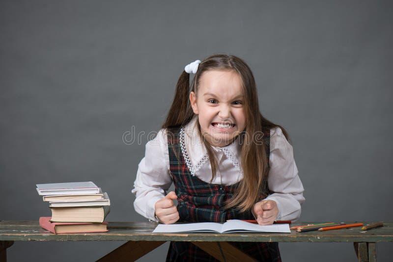 Behandla som ett barn flickan i ett sammanträde för skolalikformig på en tabell med böcker royaltyfria bilder