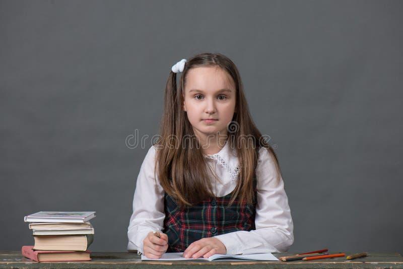 Behandla som ett barn flickan i ett sammanträde för skolalikformig på en tabell med böcker arkivbilder