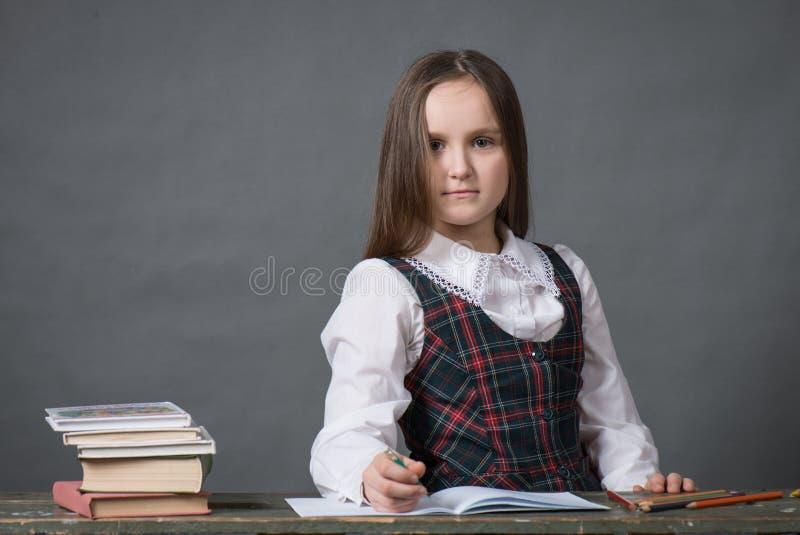 Behandla som ett barn flickan i ett sammanträde för skolalikformig på en tabell med böcker fotografering för bildbyråer