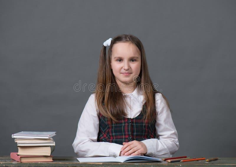 Behandla som ett barn flickan i ett sammanträde för skolalikformig på en tabell med böcker royaltyfria foton