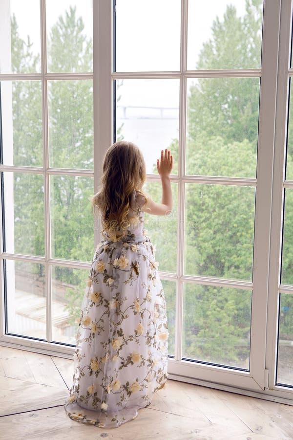 Behandla som ett barn flickan i långa ställningar för en blom- klänning royaltyfri bild