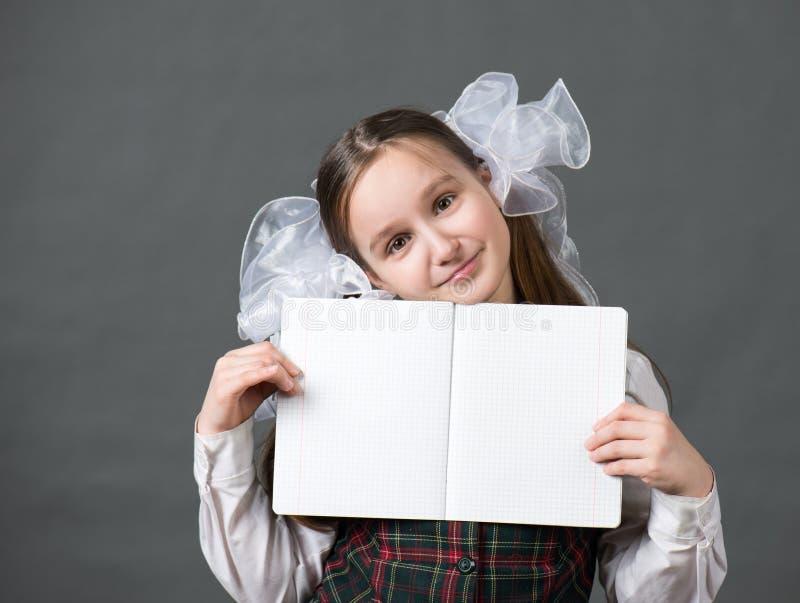 Behandla som ett barn flickan i skolalikformig med vita pilbågar royaltyfria bilder
