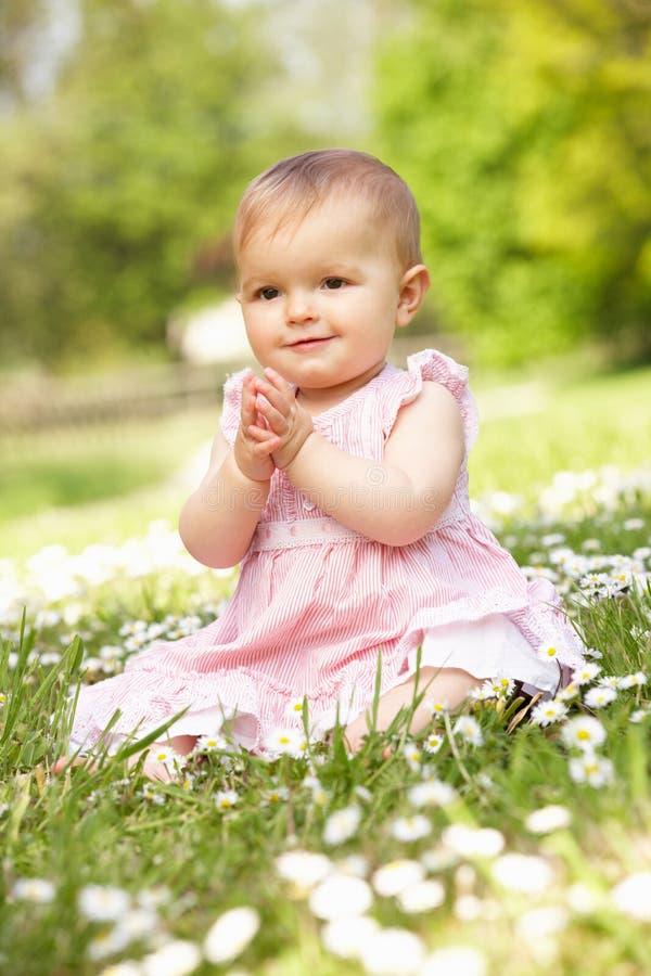 Behandla som ett barn flickan i sommarklänningen som sitter i fält arkivfoton