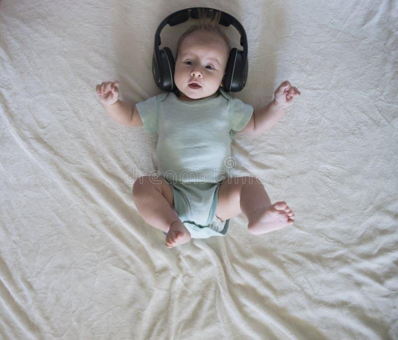 Behandla som ett barn flickan i stor hörlurar fotografering för bildbyråer