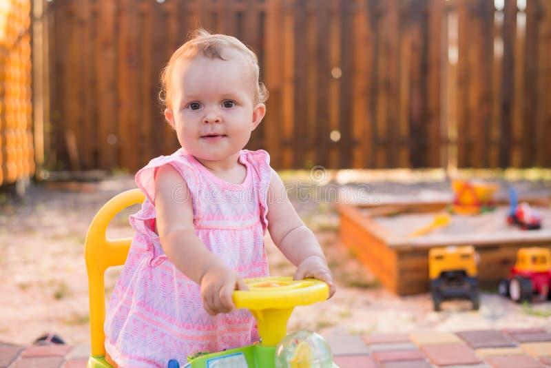 Behandla som ett barn flickan som kör en leksakbil på den utomhus- lekplatsen arkivbilder