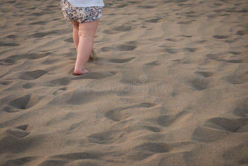 Behandla som ett barn flickan kör på sand arkivbilder