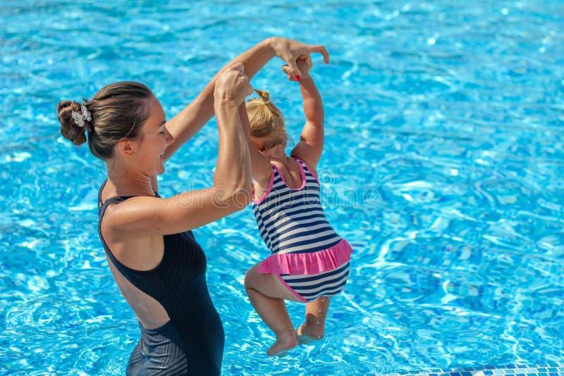 Behandla som ett barn flickan lär att simma i pöl med hennes moder royaltyfria bilder