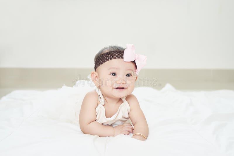 Behandla som ett barn flickan som ler på golvet som isoleras på vit royaltyfria foton