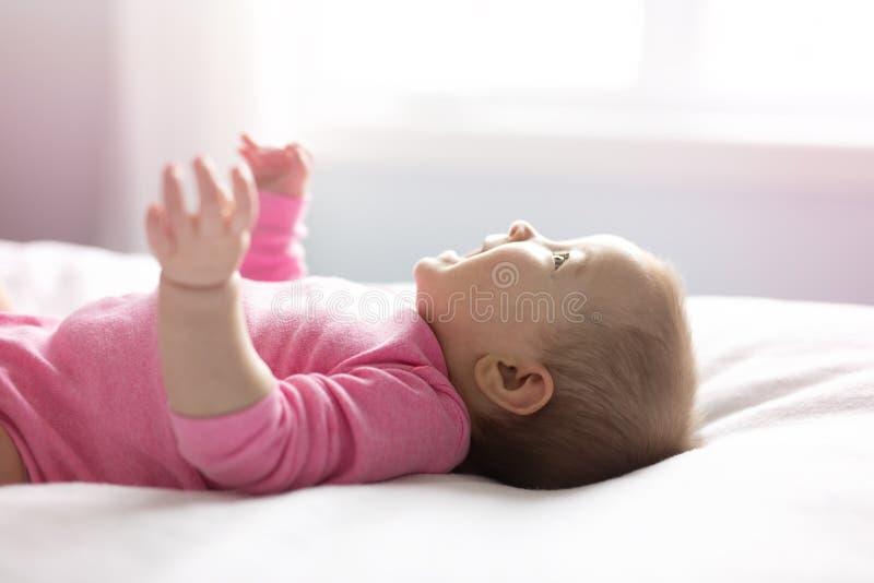 Behandla som ett barn flickan som ligger på det vita arket på sovrummet arkivbild