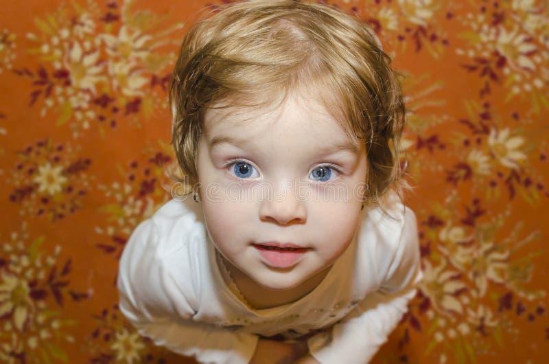 Behandla som ett barn flickan med blåa ögon arkivfoto
