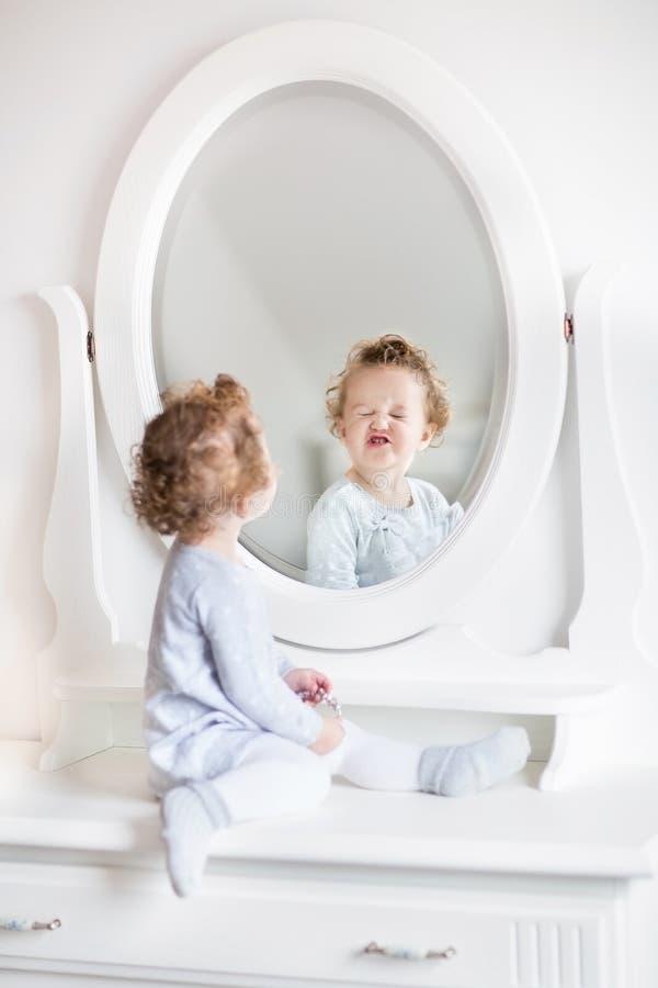 Behandla som ett barn flickan med den nästa rundan för lockigt hår i spegel royaltyfria foton