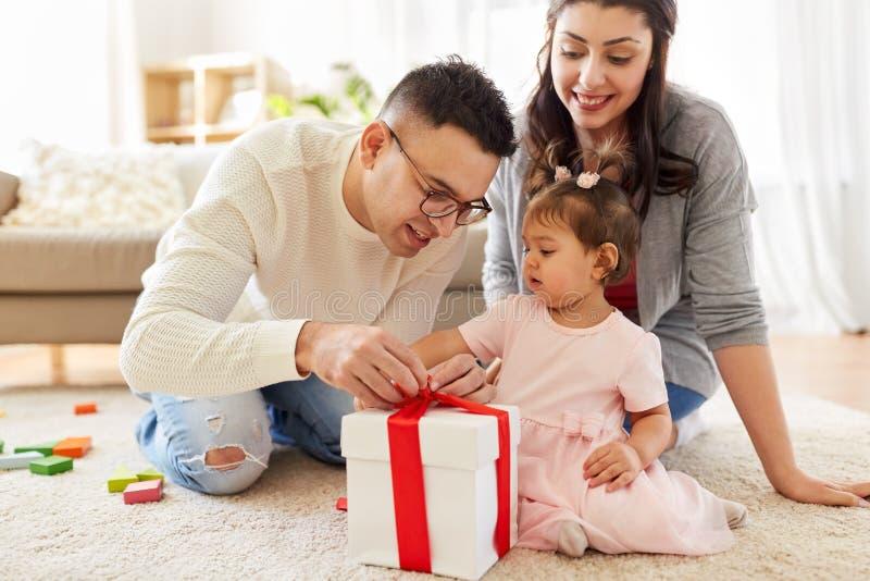 Behandla som ett barn flickan med födelsedaggåvan och föräldrar hemma royaltyfri foto