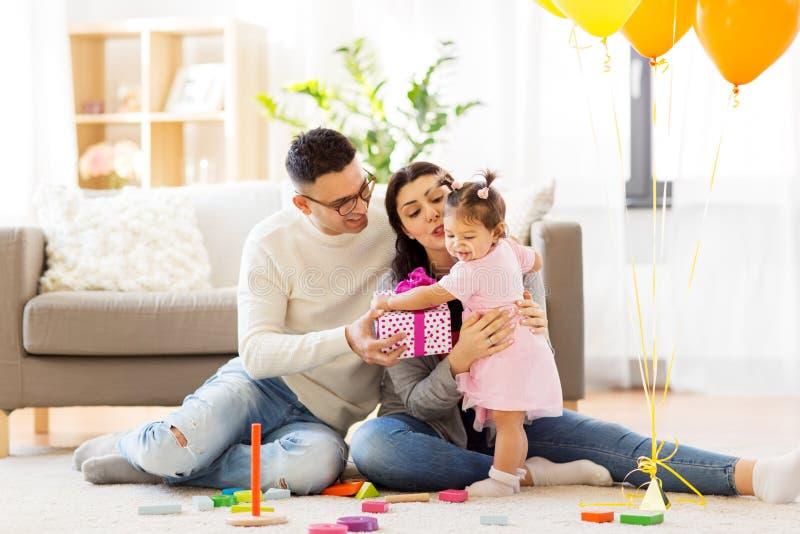 Behandla som ett barn flickan med födelsedaggåvan och föräldrar hemma royaltyfri fotografi