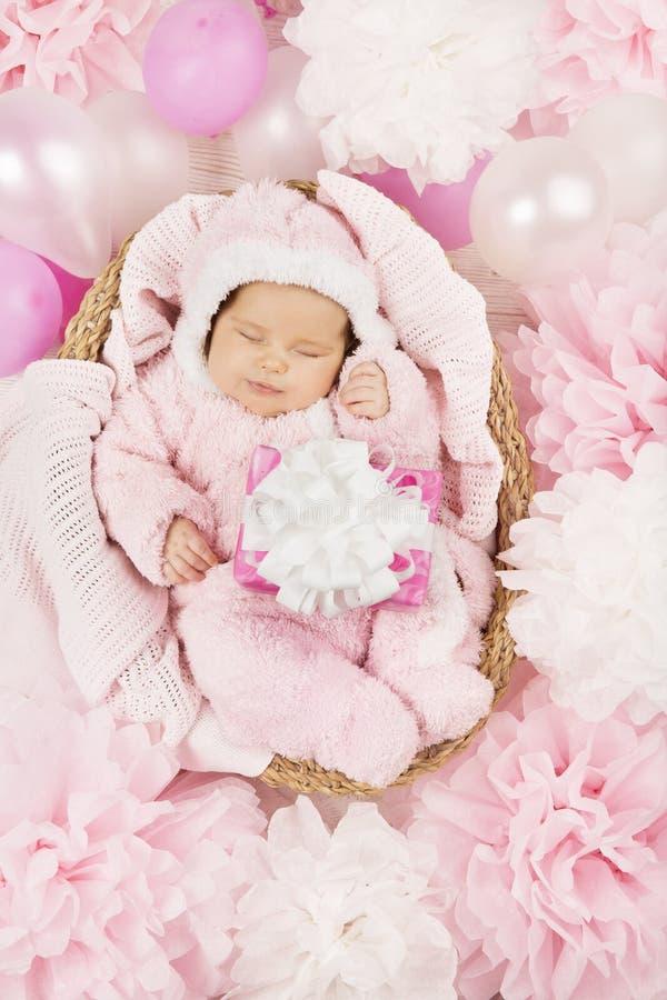 Behandla som ett barn flickan med gåvan som sover, födelsedag för nyfött barn royaltyfria bilder