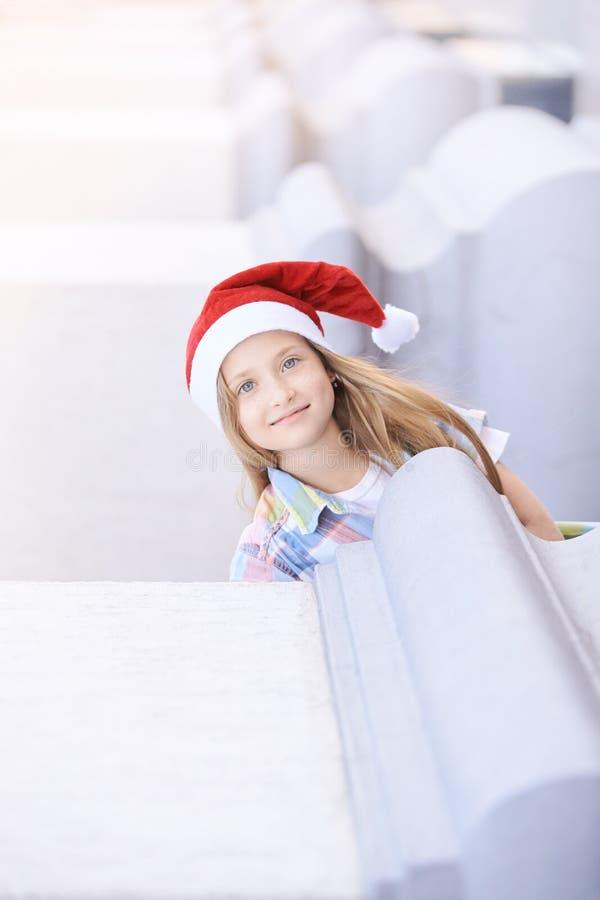 Behandla som ett barn flickan med hatten för det nya året le för julbarn som är utomhus- arkivfoto