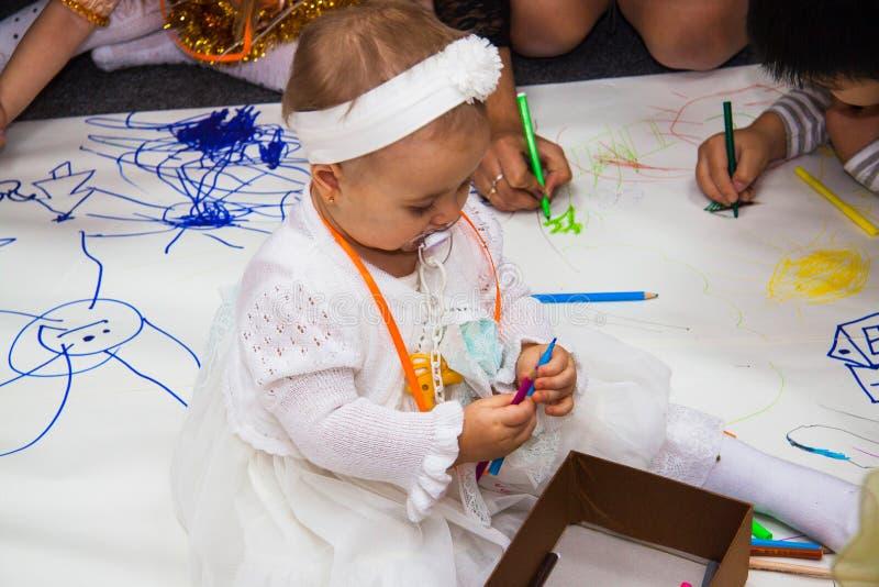 Behandla som ett barn flickan med mamman på teckningskursen arkivfoton