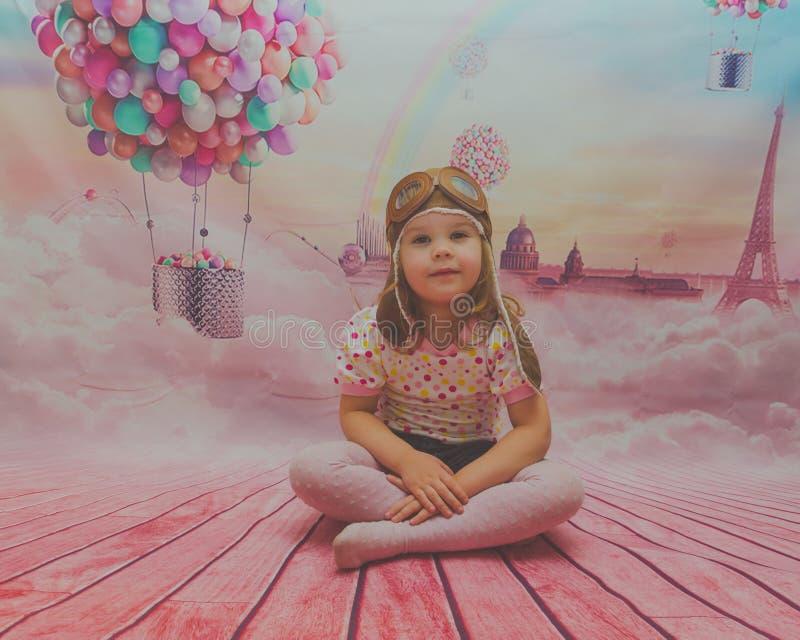 Behandla som ett barn flickan på bakgrunden av ballongen till den pilot- hjälmen för ` s arkivfoto