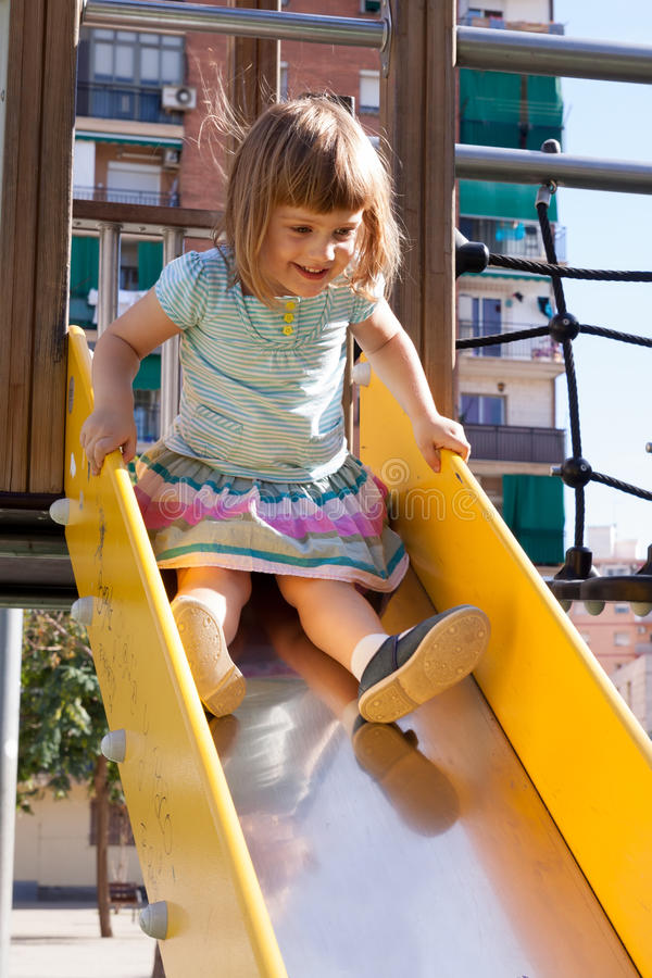 Behandla som ett barn flickan   på glidbana på lekplatsområde arkivfoton