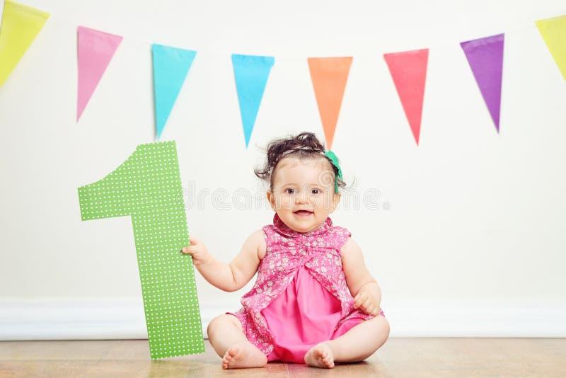 Behandla som ett barn flickan på hennes första födelsedagparti royaltyfria foton