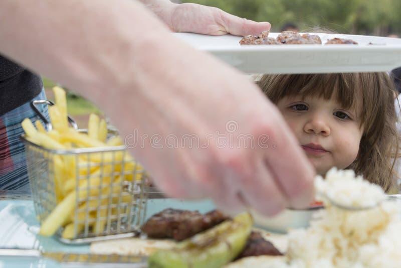 Behandla som ett barn flickan på matställetabellen royaltyfria bilder