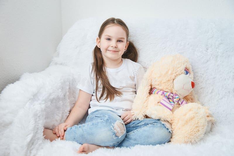 Behandla som ett barn flickan som sitter på den vita soffan i vit t-skjortor och jeans Banny mjuk plysch fotografering för bildbyråer