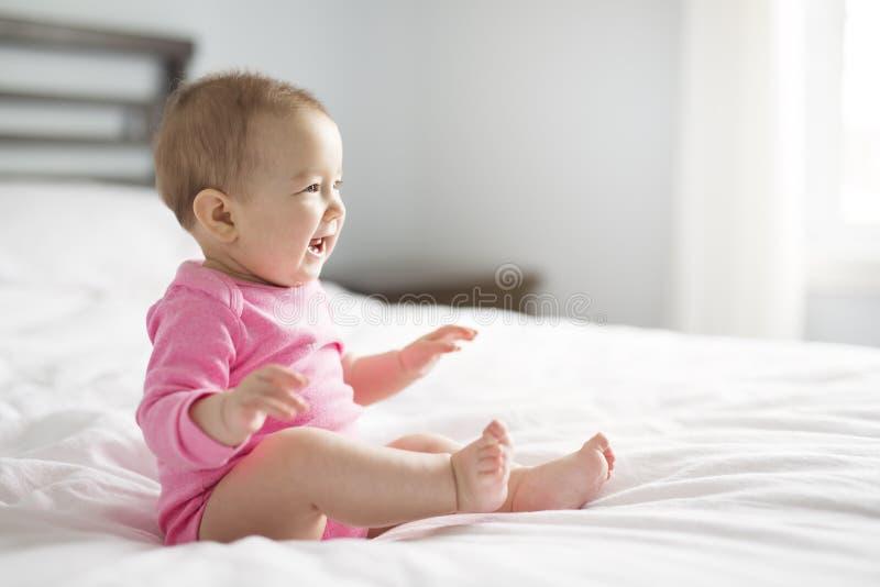 Behandla som ett barn flickan sitter på det vita arket på sovrummet royaltyfri fotografi